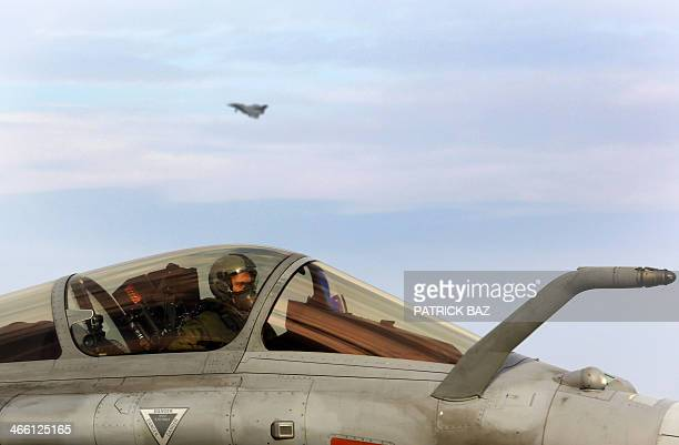A French Navy pilot sits in the cockpit of his Rafale jet fighter while another tries to land on the deck of the French aicraft carrier Charles de...