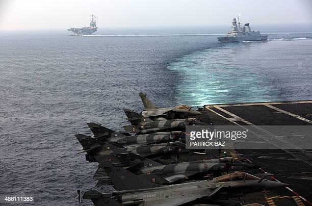 French Navy Rafale fighter jets sit on the flight deck of the Charles de Gaulle escorted by French fregate Forbin while the US Navy aircraft carrier...