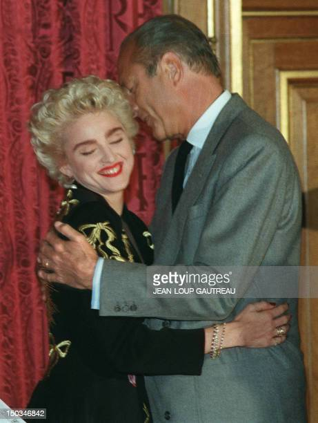 French neoGaullist Prime Minister and Paris Mayor Jacques Chirac hugs warmly Italianborn USpop idol Madonna 28 August 1987 at Paris City Hall during...