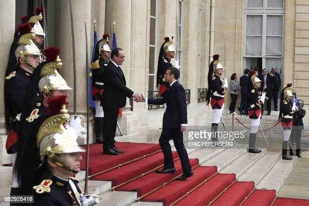 French newly elected President Emmanuel Macron is welcomed by his predecessor Francois Hollande as he arrives at the Elysee presidential Palace for...