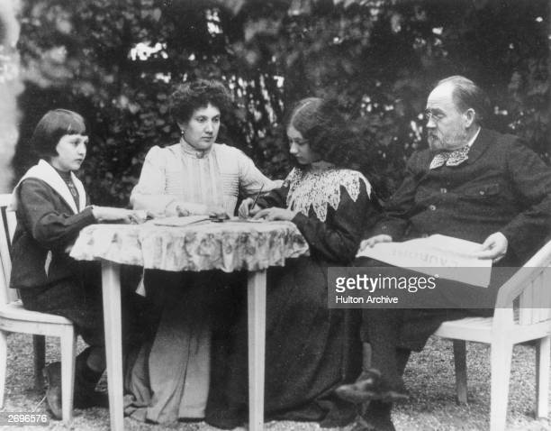 French novelist Emile Zola reading L'Aurore' newspaper at home with his family in VerneuilsurSeine Left to right Jacques Zola's wife Jeanne Denise...