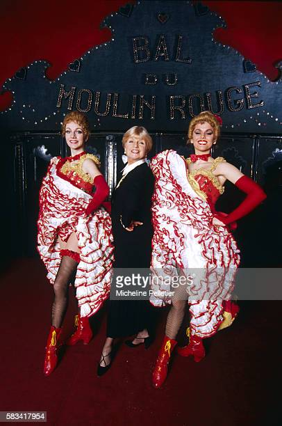 French novelist Francoise Dorin poses between two cancan dancers on the stage of the Parisian Moulin Rouge cabaret