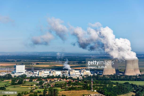 vista aerea della centrale nucleare francese nel paesaggio rurale in estate con torri di raffreddamento fumanti sul cielo blu - atomic imagery foto e immagini stock