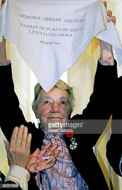 French nun Yvonne Pierron holds up a white headscarf the symbol of Madres de Plaza de Mayo after receiving 14 July 2005 the Legion d'Honneur at the...