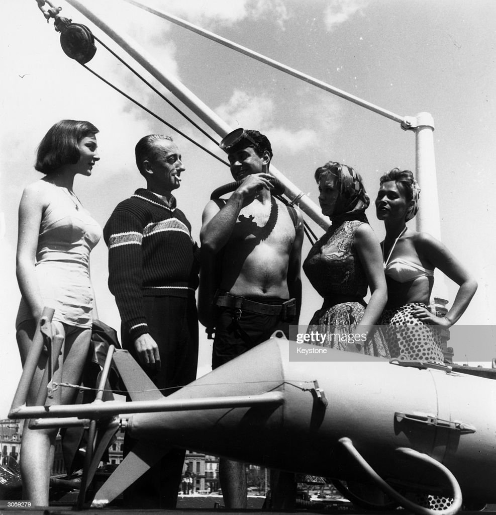 French oceanographer Jacques Cousteau (1910 - 1997) hosts a party on board his research vessel 'Calypso' before the showing of George Clouzot's film 'Le Monde Du Silence' at the Cannes Film Festival. Present are (left to right) Edith Zetline, Cousteau, crew member Albert Falco and actresses Isabelle Corey and Bella Darvi (1926 - 1971).