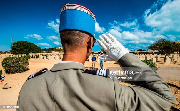 A French officer gives a salute before an Allied grave during a ceremony at El Alamein War Cemetary marking 75 years since the pivotal WWII battle in...