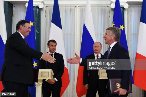 French oil giant Total Chief Executive Officer Patrick Pouyanne exchanges documents with Novatek chief Leonid Mikhelson as Russian President Vladimir...