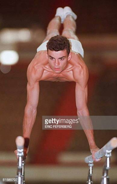 French Olympic team gymnast Eric Poujade practices on the parallel bars during a training session 13 July at Auburn University in Auburn Alabama The...