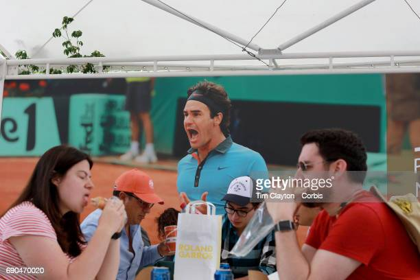 French Open Tennis Tournament Day Three Fans eating in the dining area of Roland Garros as an image of Roger Federer hangs as a backdrop at the 2017...