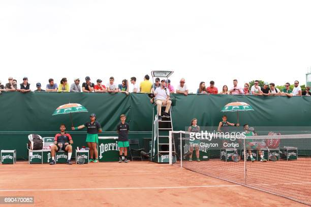 French Open Tennis Tournament - Day Three. Laurent Lokoli of France and winner Martin Klizan of Slovakia sit during an end change during a tension...