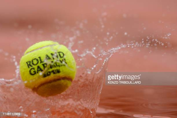 French Open tennis tournament official ball bounces on a cover as rain falls on day eleven of The Roland Garros 2019 French Open tennis tournament in...