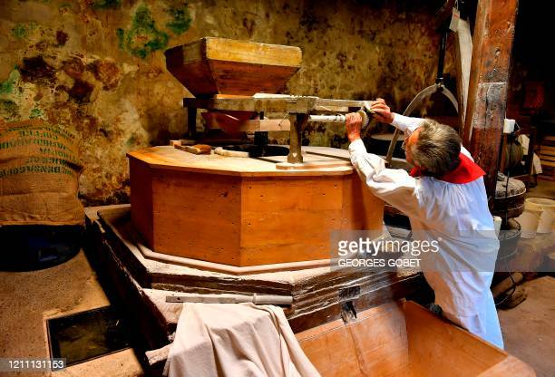 French organic flour producer Elie Coustaty checks the quality of his flour as he works in his 14th century water powered mill in Vezac near Sarlat...