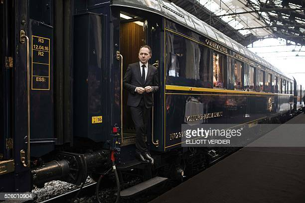 French Orient Express president Patrick Ropert stands on the edge of a door of the Orient Express train where his dishes will be served during the...