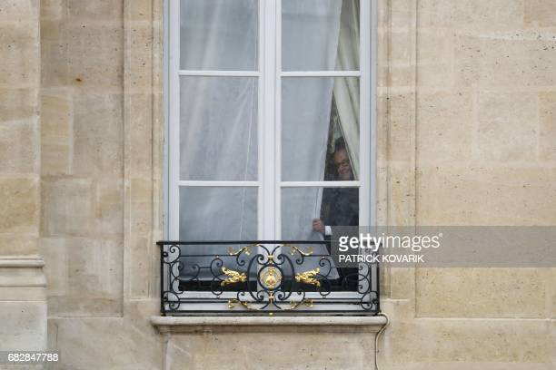 TOPSHOT French outgoing president Francois Hollande looks out from a window of the Elysee presidential Palace prior to his successor's formal...