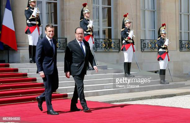 French outgoing President Francois Hollande walks with his successor Emmanuel Macron as he leaves the Elysee presidential Palace at the end of the...