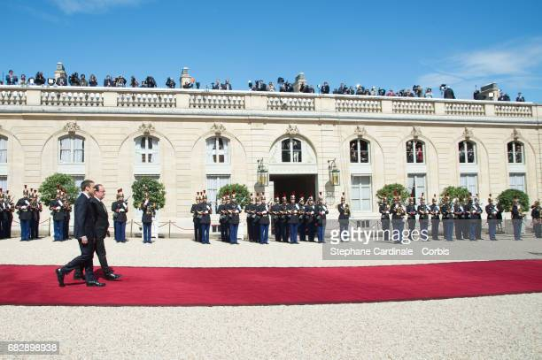 French outgoing President Francois Hollande walks with his successor Emmanuel Macron on the red carpet as he leaves the Elysee presidential Palace at...