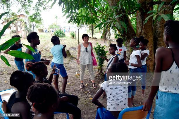 French Overseas Minister Annick Girardin speaks with teenagers in Maripasoula French Guiana during the visit of French President Emmanuel Macron on...