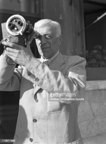 French painter Georges Braque wearing a lightcoloured suit shooting with a cinecamera Venice 1948