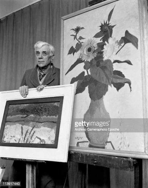 French painter Georges Braque wearing an overalls behind two paintings one with a landscape and one with a pot of sunflowers Paris 1950