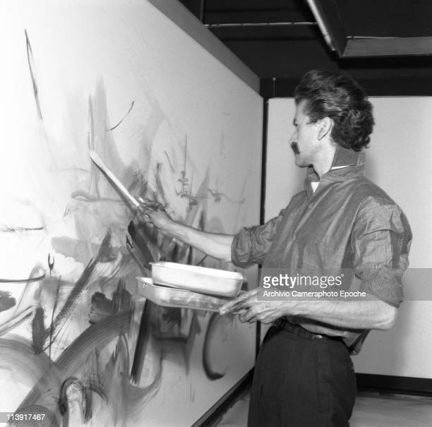 French painter Georges Mathieu painting on a wall with a paintbrush holding paint basins at the Cavallino gallery Venice 1960