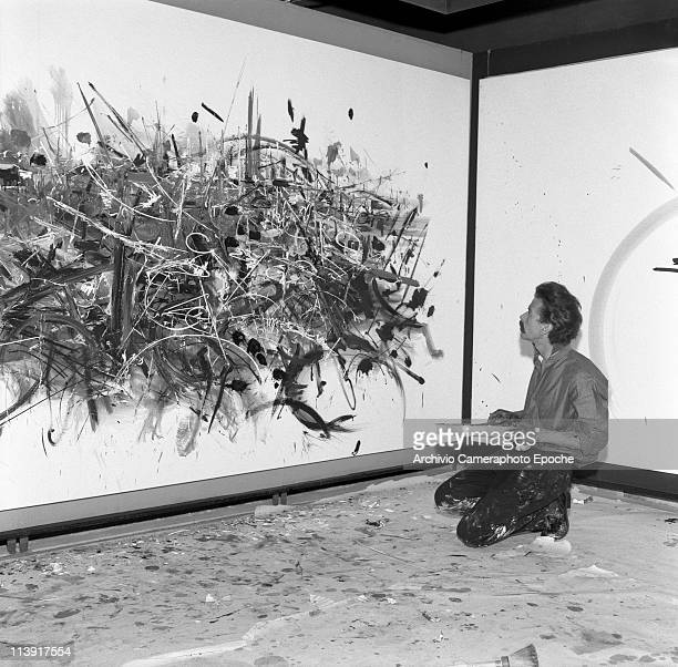 French painter Georges Mathieu sitting on his knees next to a painting on the wall wearing paintstained trousers holding a paint basin at the...
