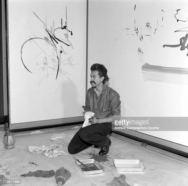 French painter Georges Mathieu sitting on his knees watching his paintings with two painted wall on his back a wine bottle on the floor basins...