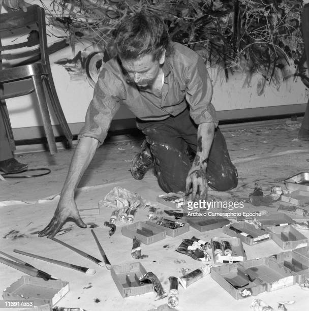 French painter Georges Mathieu with a painting on the wall behind him sitting on his knees paintstained choosing tube colours and paintbrushes on the...