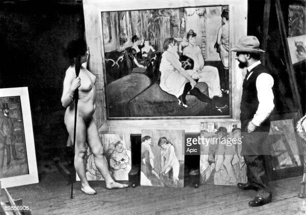 French painter Henri de ToulouseLautrec in his workshop in Paris with a model in front of his canvas 'Salon de la rue des Moulins' 1894
