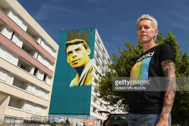 French painter Pink Art Roz poses in front a giant mural of Belgian singer Jacques Brel in Vesoul, eastern France, on August 3, 2019. - The giant...