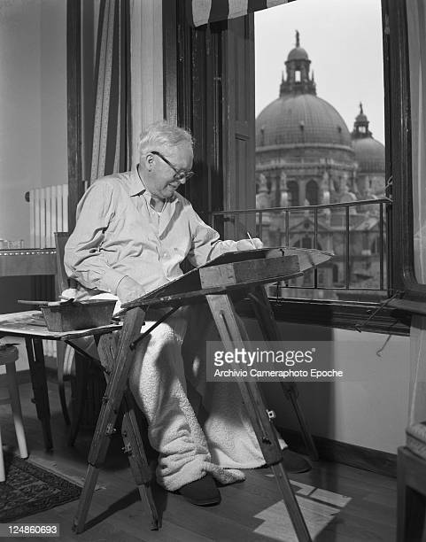 French painter Raul Dufy wearing a ciphered shirt and wrapped in a woolen blanket portrayed while sitting at the window and painting the view Venice...