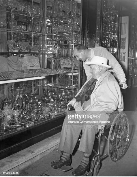 French painter Raul Dufy wearing a suit a tie a hat and wrapped into a plaid blanket sitting on a wheelchair and portrayed while watching a glass...