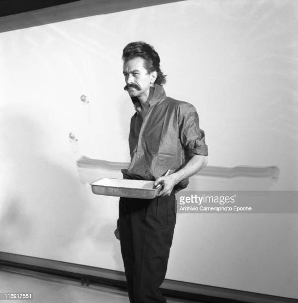 French painter standing in front of a painted wall focusing on another painting holding a paint basin at the art gallery Cavallino Venice 1960