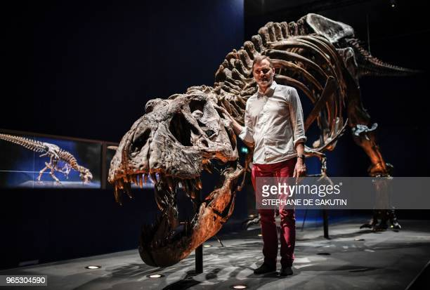 French paleontologist Ronan Allain poses in front of a skeleton of a Tyrannosaurus Rex dinosaur on June 1 2018 displayed at the French National...
