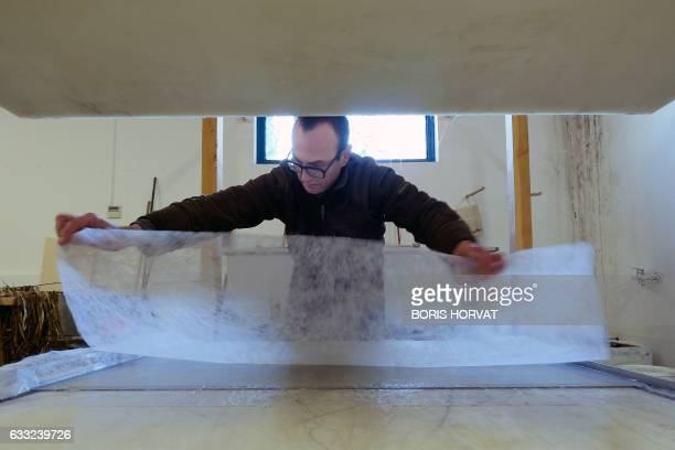 French papermaker Benoit Dudognon make a Washi, a japanese paper,from mulberry tree fibers on January 25, 2017 in Arles, southern France. Standing...