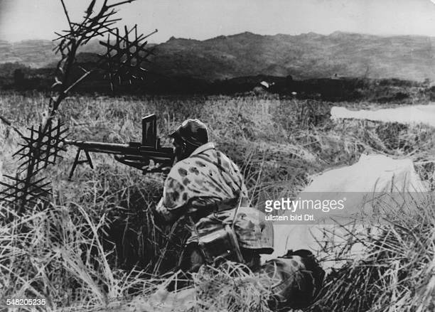 French paratrooper takes position with his machine gun shortly after landing; the paratroops were deployed behind the lines of the Viet Minh to...