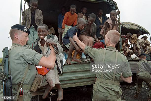 French paratroopers help some 160 Rwandan orphans on July 16 1994 at their arrival at Goma airport after they were evacuated from Gisenyi