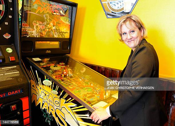 French parliamentary election UMP candidate Nadine Morano poses as she plays to pinball machine after distributing electoral leaflets on a market on...