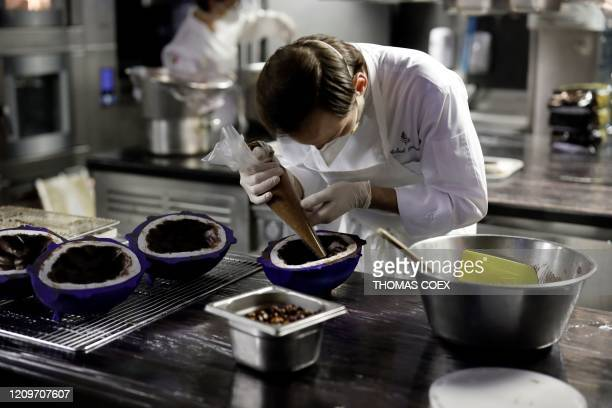 """French Pastry Chef Michael Bartocetti prepares a chocolate Easter egg for employees of a Parisian hospital in the kitchen of """"Le Cinq"""" restaurant at..."""