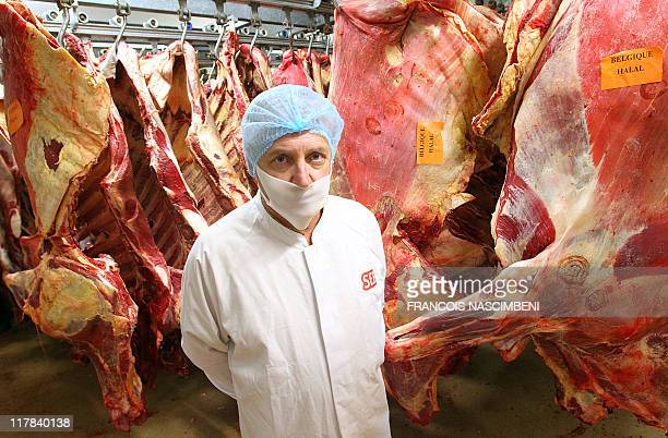 French Patrice Monguillon head of the French company SEB in SaintDizier eastern France is pictured on June 16 in front of beef carcasses before they...