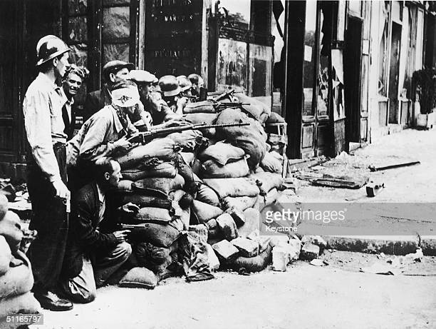 French patriots armed with machine guns rifles and pistols waiting behind a street corner barricade in Paris for any German soldiers who might come...