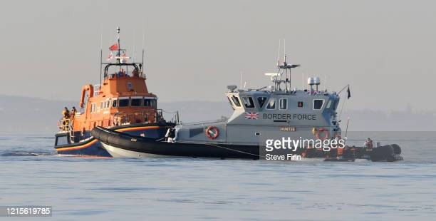 French patrol boat escorts a dinghy to the English Border Force on the English Channel, 12 miles from Dover on May 27, 2020 at sea. The dingy was...