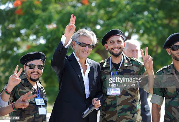 French Philosopher Bernard HenrI Levy poses with pro National Transitional Council combattants at the Tripoli Medical center on September 15 2011 in...