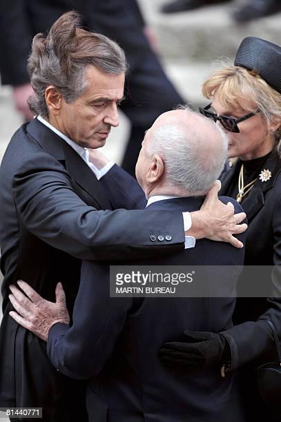 French philosopher Bernard-Henri Levy hugs Pierre Berge , longtime companion of Yves Saint-Laurent, next to his wife artist Arielle Dombasle, on June...