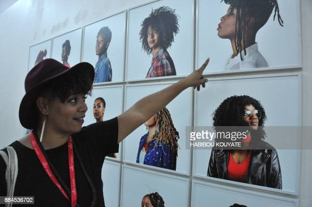 French photographer Helene Jayat points to her work during the opening of the 11th Rencontres de Bamako' the African Biennale of Photography in...