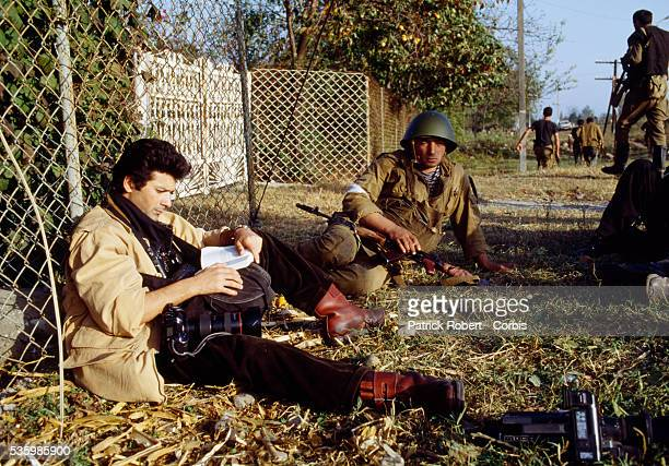 French photographer Patrick Robert catches up on some reading during a break in the fighting on the disputed Abkhazia front during the Georgian Civil...
