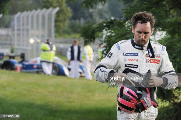 French pilot Franck Montagny of the Peugeot HDI FAP n°2 leaves his car after giving up the Le Mans 24hour endurance race on June 13 due to a start of...
