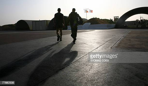 A French pilot of a Mirage F1 fighter plane F1 with his engineer walk on the runway to his plane before taking off for a daily mission over the...