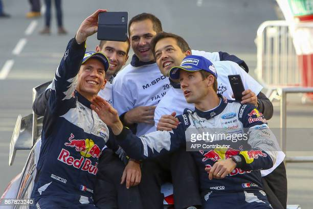 French pilot Sebastien Ogier and co pilot Julein Ingrassia of MSport World Rally Team take a selfie photograph as they celebrate with the MSport team...