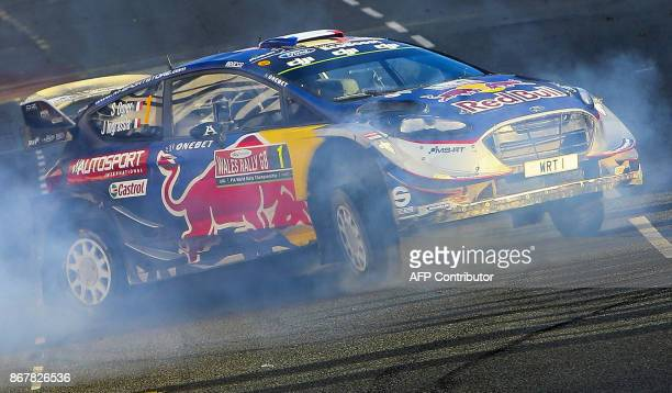 TOPSHOT French pilot Sebastien Ogier and co pilot Julein Ingrassia of MSport World Rally Team celebrate by 'pulling doughnuts' after winning the 2017...