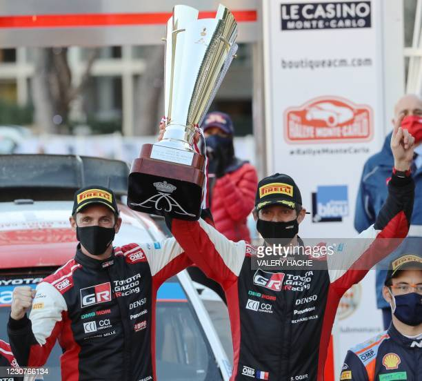 French pilot Sebastien Ogier and co-pilot Julien Ingrassia hold the winners' trophy on the podium of the WRC season-opening Monte Carlo Rally on...